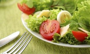 Leafy green salad with eggs and tomatoes.