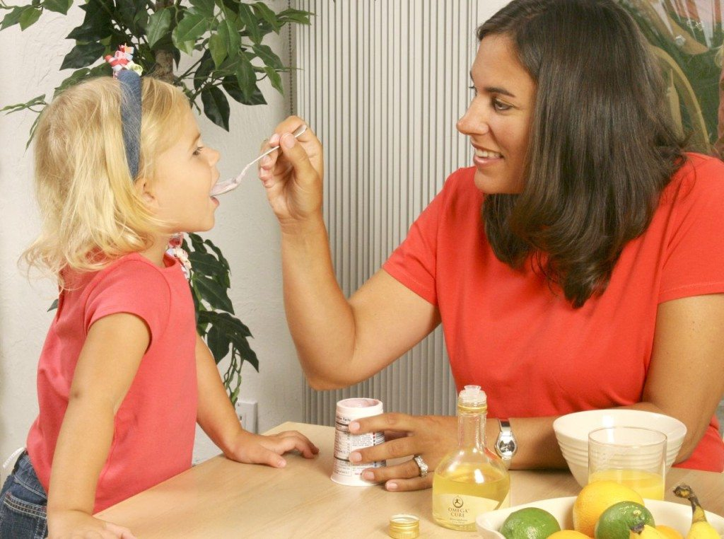 Mother feeding daughter Omega Cure fish oil on a spoon