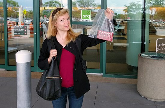 Young woman holding Omega Cure Extra Strength in ziplock bag